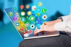Remettez presser l'ordinateur portable moderne avec les icônes mobiles et les symboles d'APP Photos stock