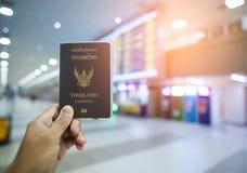 Remettez qui montrent le passeport de la Thaïlande à l'aéroport Photographie stock
