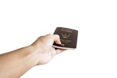 Remettez recevoir ou donner le passeport thaïlandais, foyer sélectif, d'isolement sur le fond blanc Photos stock