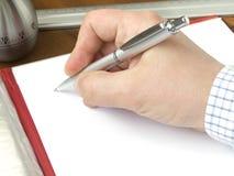 Remettez retenir un crayon lecteur et une feuille d'un papier s'étendant en fonction Photographie stock libre de droits