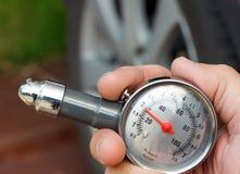 Remettez retenir un indicateur de pression de pneu Image libre de droits