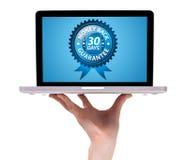 Remettez retenir un ordinateur portatif avec le dos 30 d'argent Photos libres de droits