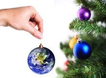 Remettez s'arrêter vers le haut de la décoration de la terre sur l'arbre de Noël images stock