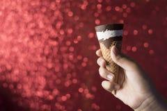Remettez se tenir/montrant le cône de chocolat et de glace à la vanille avec le fond rouge brillant Photos libres de droits