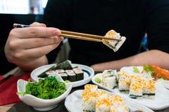Remettez tenir bâtons chinois/japonais et un morceau de sushi, de table pleine des sushi et d'algues Photographie stock libre de droits