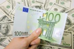 Remettez tenir cent euros, beaucoup d'argent (les dollars d'États-Unis) Photographie stock
