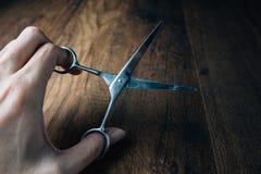 Remettez tenir de vieux ciseaux sur une table de travail en bois Image libre de droits