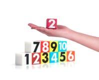 Remettez tenir des nombres en plastique colorés sur le fond blanc, NO1 Photo stock