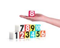 Remettez tenir des nombres en plastique colorés sur le fond blanc, NO1 Image libre de droits