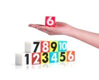 Remettez tenir des nombres en plastique colorés sur le fond blanc, NO1 Images libres de droits