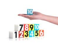 Remettez tenir des nombres en plastique colorés sur le fond blanc, No10 Image libre de droits