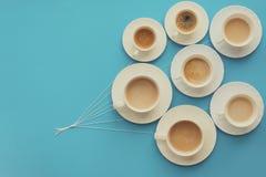 Remettez tenir des tasses de café avec du lait et sans dans la forme des ballons sur le fond de papier bleu Concept de temps Macr Photo libre de droits