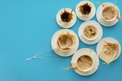 Remettez tenir des tasses de café avec du lait et sans dans la forme des ballons sur le fond de papier bleu Concept de temps Macr Photos libres de droits