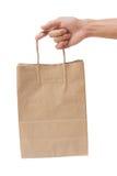 Remettez tenir et donner le sac de papier d'isolement au-dessus du fond blanc Photographie stock