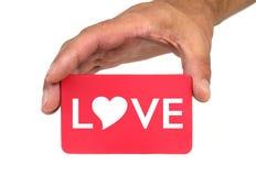 Remettez tenir et montrer une carte rouge avec le texte d'AMOUR et la forme de coeur Photos libres de droits