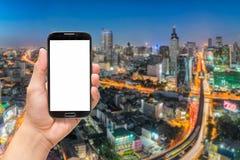 Remettez tenir l'écran vide téléphone intelligent avec le fond de ville Images stock