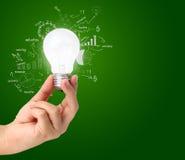 Remettez tenir l'ampoule avec des diagrammes et des graphiques de dessin Photos stock