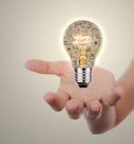 Remettez tenir l'ampoule avec le concept d'affaires à l'intérieur illustration stock