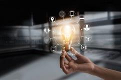Remettez tenir l'ampoule avec les multimédia d'icônes et la connexion réseau de client Image stock