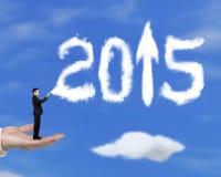 Remettez tenir l'homme d'affaires pulvérisant la flèche 2015 vers le haut des nuages avec le ciel Photographie stock