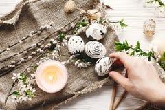 Remettez tenir l'oeuf de pâques peint élégant au backgro en bois rustique photo libre de droits