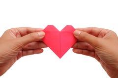 Remettez tenir l'origami rouge de papier de coeur sur le fond blanc Photographie stock libre de droits