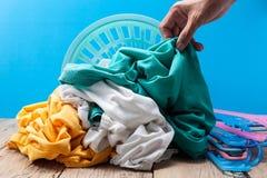Remettez tenir la blanchisserie sale dans le panier de lavage sur la planche en bois, bleue photographie stock