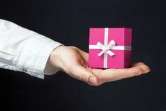 Remettez tenir la boîte pour un cadeau d'isolement sur le noir images stock