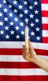 Remettez tenir la bougie allumée avec brouillé le drapeau des Etats-Unis à l'arrière-plan Photographie stock libre de droits
