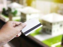 Remettez tenir la carte de crédit au-dessus du fond brouillé du modèle de maison Image stock
