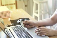 Remettez tenir la carte et à l'aide de l'ordinateur portable pour des achats et le paiement en ligne Images libres de droits