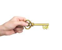 Remettez tenir la clé d'or de trésor dans la forme de symbole de livre Images stock