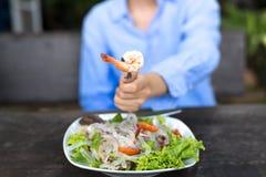 Remettez tenir la fourchette avec de la salade de nouille de crevette rose et en verre Images libres de droits