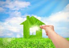 Remettez tenir la maison verte avec le champ et le fond de ciel bleu Image stock