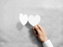 Remettez tenir la maquette blanche vide de carte du ` s de valentine Images stock