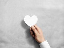 Remettez tenir la maquette blanche vide de carte du ` s de valentine Photographie stock libre de droits