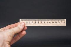 Remettez tenir la petite règle en bois sur un fond noir Photographie stock