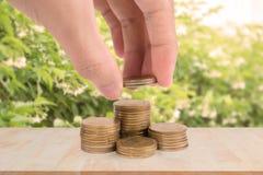 Remettez tenir la pièce de monnaie d'argent d'or avec l'argent d'économie et l'élevage Photographie stock
