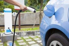Remettez tenir la prise pour le remplissage d'une voiture électrique dans la station thermale de stationnement Image libre de droits