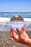 Remettez tenir la sphère en verre à la plage et à la mer photos libres de droits