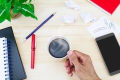 Remettez tenir la tasse de café chaude avec le smartphone, papier chiffonné, verres, carnets, stylo, crayon, trombones, pot de fe Images libres de droits