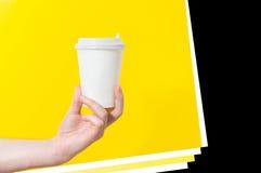 Remettez tenir la tasse de thé de papier de café sur le fond jaune, maquette, Images libres de droits