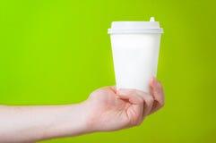 Remettez tenir la tasse de thé de papier de café sur le fond vert, la maquette, T Photos libres de droits