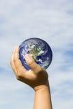 Remettez tenir la terre bleue sur le nuage et le ciel Éléments de cette image Photo libre de droits