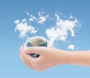 Remettez tenir la terre sur le fond de carte de nuages du monde, éléments de t Images libres de droits