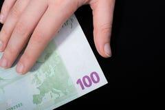 Remettez tenir le billet de banque de l'euro 100 sur un fond noir Image libre de droits