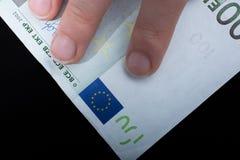 Remettez tenir le billet de banque de l'euro 100 sur un fond noir Images stock