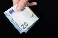 Remettez tenir le billet de banque de l'euro 100 sur un fond noir Photographie stock libre de droits