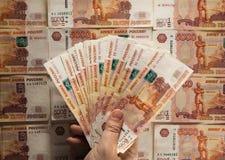 Remettez tenir le billet de banque russe, sur le fond russe d'argent Image libre de droits