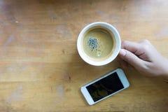 Remettez tenir le café d'expresso dans la tasse blanche avec le téléphone intelligent et copiez l'espace Photo libre de droits